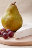 Green pear, cheese brie, red grapes on board Stock Photos