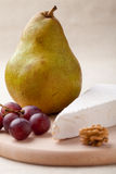 Green pear, cheese brie, walnut, grapes Stock Photography