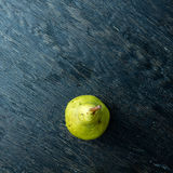 Green pear on a dark background Stock Images