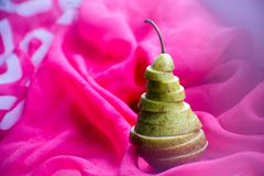 Green pear. Draping pink silk. Scene for drawing objects Stock Photo