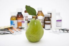 Green pear in front of pills Royalty Free Stock Image