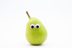 Green pear with googly eyes on white background Royalty Free Stock Images