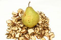 Green pear lying on dried fruits Royalty Free Stock Image