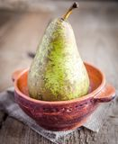 Green pear in rustic decor Royalty Free Stock Photography