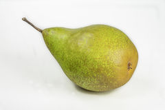 Green pear on a table on a white background. Green pear closeup on white background Stock Photos