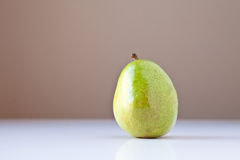 Green Pear on White with Brown Background Royalty Free Stock Photography