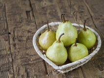 Green pears in basket on rustic brown wooden table. Royalty Free Stock Photo