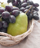 Green pears and black grapes in a basket Royalty Free Stock Photos
