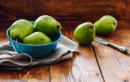 Green Pears in Blue Bowl. And Some Pears on Background with Knife Royalty Free Stock Images