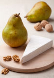 Green pears, cheese brie, cores of walnuts Royalty Free Stock Photo
