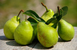 Green pears. On a wooden table stock photos