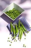 Green peas. With white bowl and napkin purple stock photo