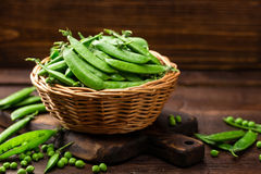 Green peas. In basket on wooden table Stock Photo