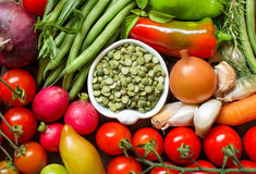 Green peas in a bowl between fresh vegetables Stock Images