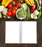 Green peas in a bowl with fresh vegetables and notebook Stock Image