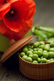 Green peas in bowl on wooden background with red poppy Royalty Free Stock Photos