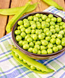 Green peas in brown bowl on checkered napkin Stock Images