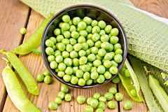 Green peas in brown bowl with napkin on board Royalty Free Stock Photos