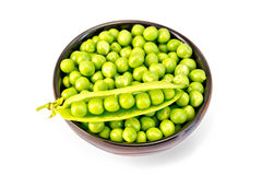 Green peas in brown bowl with pod Stock Images