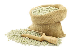 Green peas in a burlap bag with a wooden scoop Stock Photo