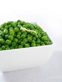 Green peas with butter. Bowl of peas on a white background garnished with melting butter stock photos