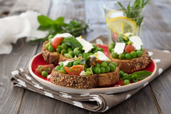 Green peas with cherry tomatoes, feta cheese and mint on toast Stock Image