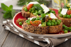 Green peas with cherry tomatoes, feta cheese and mint on toast Stock Photos