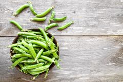 Green peas in a dish. Green peas in a clay plate on a wooden table. It lies next to pea pods Stock Photo