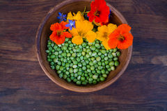 Green peas and colorful edible flowers in clay bowl Royalty Free Stock Images