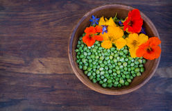 Green peas and colorful edible flowers in clay bowl Royalty Free Stock Photography