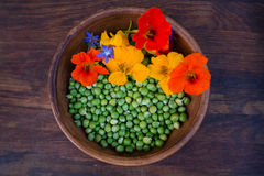 Green peas and colorful edible flowers in clay bowl Royalty Free Stock Image