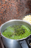 Green peas cooking in silver colored metal pot Royalty Free Stock Photography