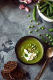 Green peas cream puree soup in dark plate. Vegetarian green cream soup of green peas with seeds and bread on grey background. Top stock photography
