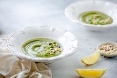 Green peas cream puree soup in white plate. Vegetarian green cream soup of green peas with seeds and lemon on grey background. Top. Light summer green pea cream royalty free stock photography