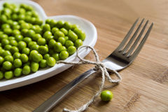 Green peas on a creative heart-shaped plate royalty free stock images