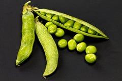 Green peas. Fresh peas on black background Stock Photos