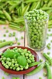 Green peas in a glass on a wooden background Stock Image