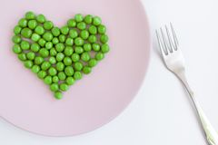 Green peas heart shaped, pink plate and a fork on white table. St. Valentine`s day concept stock images