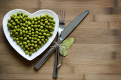 Green peas on a heart shaped plate. On wood stock photography
