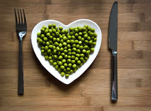 Green peas on a heart-shaped plate. Green peas on a heart shaped plate on wood royalty free stock photography