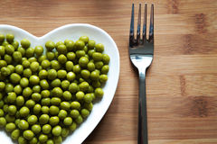 Green peas on heart-shaped plate. Green peas on a heart shaped plate on wood royalty free stock photo