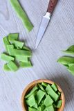 Green peas, knife and wooden bowl on table Stock Photography