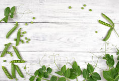 Green peas with leaves on white wooden table top view stock image