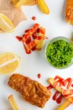 Green peas, lemon slices, fish and chips covered with barbecue sauce