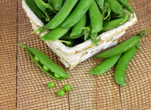 Green peas open pods on wooden background. . Close-up. Royalty Free Stock Images