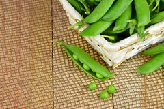 Green peas open pods on wooden background. . Close-up. Royalty Free Stock Image