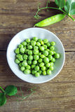 Green peas. Organic green peas in bowl on rustic wooden background - healthy organic green spring ingredient ready for cooking Royalty Free Stock Image