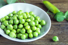 Green peas. Organic green peas in bowl on rustic wooden background - healthy organic green spring ingredient ready for cooking Stock Photo