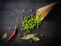 Green peas in a paper and chili peppers on a dark wooden background. Stock Image