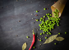 Green peas in a paper and chili peppers on a dark wooden background. Royalty Free Stock Images